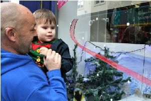 Caleb Williamson unveiling the Christmas display at the Cancer Research shop in Derry with his dad Darren