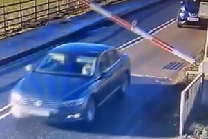 A car going under the train barrier