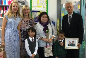 P3 pupils Lydia Briggs and Theo Souch present a picture to Thai adoption officials Miss Chintana Watcharakul and Mr Suthi Jantarawong during their visit to Dromore Central Primary School. Also pictured are teachers Miss McKeown and Mrs Mackay.