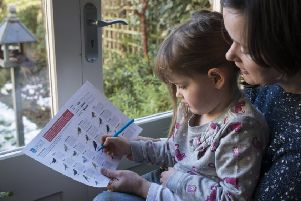RSPB Big Garden Birdwatch: a mother and her daughter counting birds in their garden SUS-190115-163021001