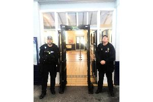 Officers and the scanning arch at the station