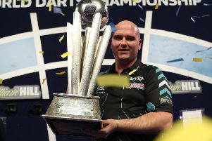 Rob Cross proudly clutches the William Hill World Darts Championship trophy. Picture courtesy Lawrence Lustig/PDC