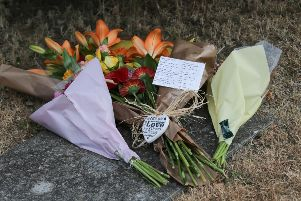Floral tributes left at the address. Photograph by Eddie Mitchell