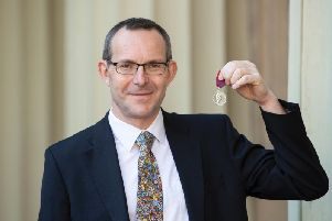 British cave diver John Volanthen poses with his award after being presented with the George Medal for rescuing those trapped in a flooded cave in Thailand, following an investiture ceremony at Buckingham Palace in London on February 26 (Photograph: Victoria Jones/AFP/Getty Images)