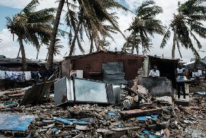 An owner (2nd R) stays at his destroyed bar after the cyclon Idai hit near the beach in Beira, Mozambique, on March 23, 2019. - The death toll in Mozambique on March 23, 2019 climbed to 417 after a cyclone pummelled swathes of the southern African country, flooding thousands of square kilometres, as the UN stepped up calls for more help for survivors. Cyclone Idai smashed into the coast of central Mozambique last week, unleashing hurricane-force winds and rains that flooded the hinterland and drenched eastern Zimbabwe leaving a trail of destruction. (Photo by Yasuyoshi CHIBA / AFP)        (Photo credit should read YASUYOSHI CHIBA/AFP/Getty Images) SUS-190104-114605003