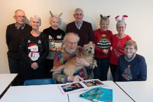 Edward Mayor examines the special book with his dog Sandy and photographic group members