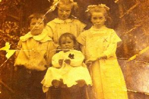 The Pickett children are pictured in front of their cottage in Church Terrace, Cubbington. The baby in the high chair is baby Iris, the boy on the left is William Pickett Jnr, known as 'Son,' and the girl at the back is Violet.