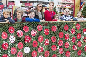 Clapham Terrace Primary School pupils, Oliver, Isaac, Rocco, Robert, Emilia and Eli with Sarah Jones from Royal Priors (centre left) and teaching assistant Jitka pose with the Poppy Exhibition created by pupils at the school and displayed at the shopping centre in 2018.