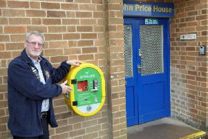 Kenilworth Lions Club President Graham Pemberton with the defibrillator outside the Kenilworth Lions Club furniture store