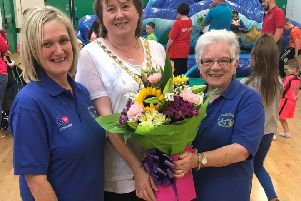 The Mayor, Cllr Maureen Morrow, presents Patricia McConnell, chairperson of Carnlough Community Association, with a bouquet of flowers , included is Joanne McIlhatton, programme co-ordinator.