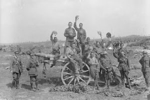 Following the capture of Grevillers by the New Zealand Division, Men of the Royal Garrison Artillery pose beside one of the 4.2 inch guns of a captured battery at Grevillers, 25 August 1918. Note the camouflage netting on the ground, which was designed to prevent the guns from being spotted from the air.