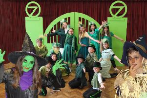 The Wicked Witch (Izzy Mattey) and Scarecrow (Ollie Harkness) in front of some of the ladies and gentlemen of the Emerald City