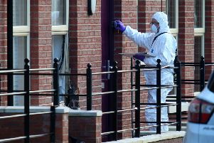 A PSNI forensics officer assesses the scene of the pipe bomb attack at Mill Street, Hilden. Pic by Pacemaker