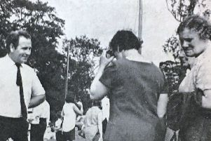 Mr R Geddis attends customers at the flower stall during the Magheragall Parish fete in 1970.