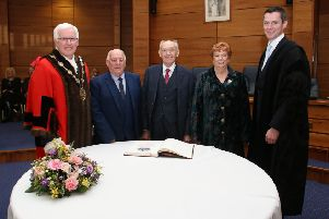 Signing the Burgess Book officially recording their new status as Freemen of the City of Lisburn and Castlereagh are Tommy Jeffers (second left), Alderman Jim Dillon MBE JP, and Geraldine Rice MBE, with the Mayor, councillor Alan Givan (left) and David Burns, chief executive (right)