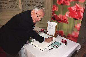 Sir Peter Bottomley signing the House of Commons Book of Remembrance SUS-181031-111350003