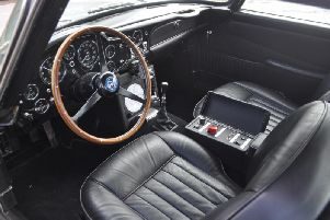The car's interior with the buttons for its gadgets by the gear stick. Picture via Coys