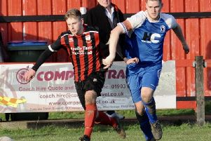 Alex Kew tangles with a Roffey player in pursuit of possession. Picture by Stephen Goodger