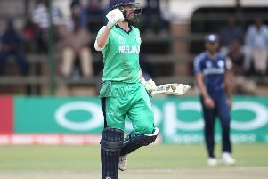 Ireland's Andrew Balbirnie punches the air as he reaches his century against Scotland
