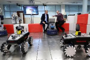 Philip Hammond (left) is shown a robot by Emmett Kerr, a lecturer in mechanical engineering, during his visit to Magee.