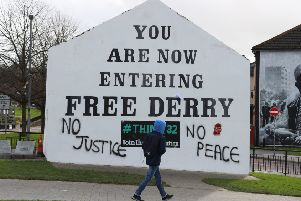A young man walks past Free Derry Corner after fresh graffiti had been put on it following the PPS announcement
