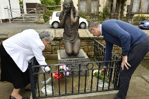 Mary Hamilton and James Miller placing flowers at the Claudy Bomb Memorial on Wednesday morning. DER3119-110KM