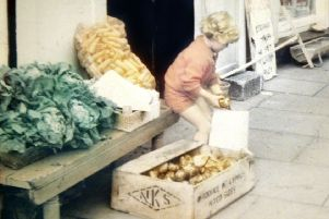 Kathryn Eakin filling a bag of potatoes outside her family store in Claudy where she was later killed by an IRA bomb, aged eight. (M McLaughlin).