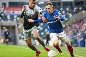 Linfield's man of the match Joel Cooper skips away from Institute's Oran Brogan.