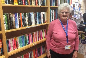 Volunteer Jean at St Barnabas Hospice bookshop in Louth prior to the flooding.