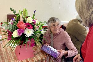 Barbara with the bouquet and chocolates donated by the community.