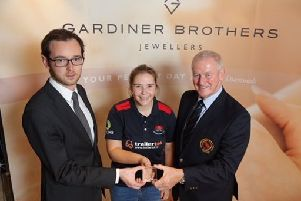 Cara Murray receives a prestigious Gardiner Brothers award from Michael Warke of Gardiner Brothers and Clarence Hiles, president of the Northern Cricket Union.