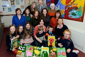 Members of Lurgan Deaf Club have created specially designed tactile books for local children who are visually impaired. Front row Blathnaid and Eibhleann Girvan, their mum Eleanor with Nessa. Ann Sterritt with her son Ben, Connal and Meadbh Bustard with Cara. Second row Alison Rooney Sensory Disability Team Manager, Adele Magill social worker, Jill McKeown Artist, Eilish Kilgallon Community Access Worker for Deaf people, Una McConville Social Worker, Back row Pat McAteer Specialist Services Manager, Southern Trust Beverley Lappin Social Worker, Kath Byrne Lurgan Deaf Club.