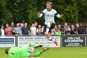 Andrew Shinnie hurdles Bedford Town keeper Alex Bennion this afternoon