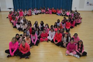 The pupils create the 'pink ribbon' - the international symbol of breast cancer awareness.