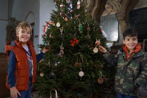 Henry and Leo with the Tealby Church tree, which features decorations made by children from the village primary school EMN-191216-091101001