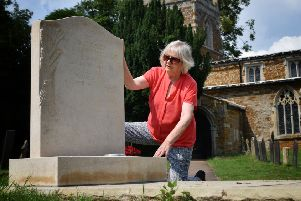 Elaine Holmes by her husband's gravestone, which she has been told to remove from Goadby Marwood Church because it did not have proper permission EMN-190724-111320001