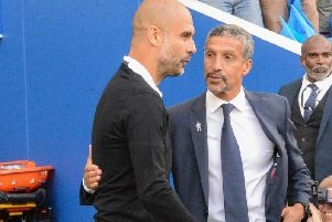 Brighton & Hove Albion manager Chris Hughton greets Pep Guardiola on the sides on Saturday. Picture by PW Sporting Pics