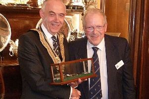 Robert Burgon, master of the Worshipful Company of Plumbers, presenting Phil Mead with the industry heritage award