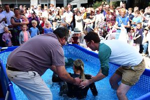 The Rev. Mark Payne (left) and Youth Leader Darren Lewis baptise one of four canadidates with total immersion outside St. Pancras Church, Chichester. Chris Hatton