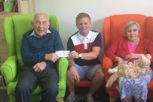 Ben Cornick, from Westbourne, presents a cheque to Sage House after completing the London Marathon for Dementia Support