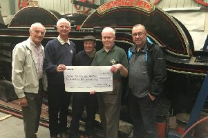 Sussex Vintage Model Railway representatives hand over their cheque to David Jones, (second from the right) project secretary and treasurer. 'From left to right they are Philip Cooke, Chairman, David Reed, Treasurer, member Tony Funnell who is also  working on the project, and Peter Bryant, Deputy Chairman. A 1930s Hornby loco stands on Beachy Head's running plate. SUS-180925-104646001