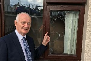Lord McCrea points to where the rock entered the bedroom window.