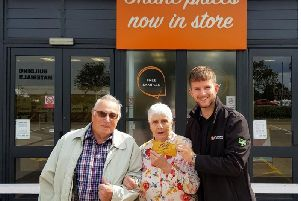 Joyce and Les Gibbs receive their prize at Flooring Superstore