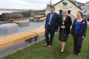 Ian McQuitty from the Department for Communities, Mayor of Causeway Coast and Glens Brenda Chivers, and Rebecca Henderson from contractor FP McCann, view some of the new paving and picnic benches