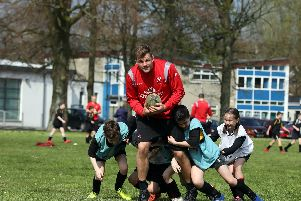 Ulster's Jordi Murphy fends off tackles from pupils at Edenderry Primary during a Kingspan Coaching Masterclass at the Portadown school