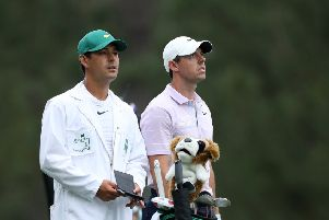 Rory McIlroy of Northern Ireland stands with caddie Harry Diamond on the 14th hole during the final round of the Masters at Augusta National Golf Club