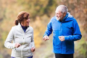 A middle aged couple exercising.