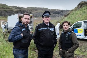 Steve (MARTIN COMPSTON), Hastings (ADRIAN DUNBAR), Kate (VICKY MCCLURE) on set in Northern Ireland. (C) World Productions - Photographer: Peter Marley