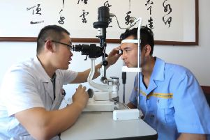 A man getting a glaucoma screening test in China from an ophthalmologist