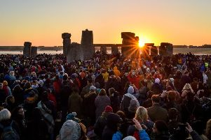 The sun rises between the stones and over crowds at Stonehenge where people gathered to celebrate the dawn of the longest day in the UK yesterday, Friday June 21, 2019. The days will now get shorter until the winter solstice on December 21. Photo: Ben Birchall/PA Wire